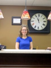 Photo of Pam at her reception desk in Luminosity Salon