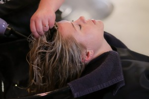 Photo of client during a highlighting color service at Luminosity Salon in Hastings, Michigan.